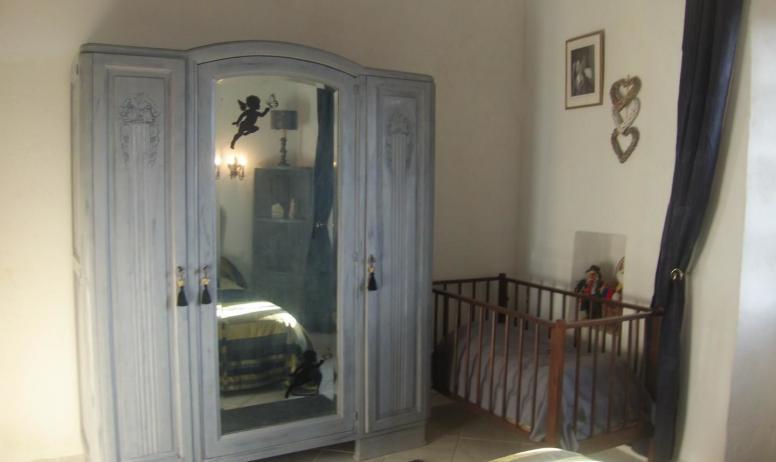 Gîtes de France - Lit bébé et armoire de la chambre