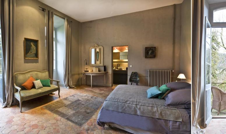 """Gîtes de France - Au Château d'Uzer, la chambre """"du Grand Salon"""", généreusement ouverte sur le parc avec ses deux grandes portes-fenêtres donnant sur le balcon, cette chambre bénéficie d'une douce lumière."""
