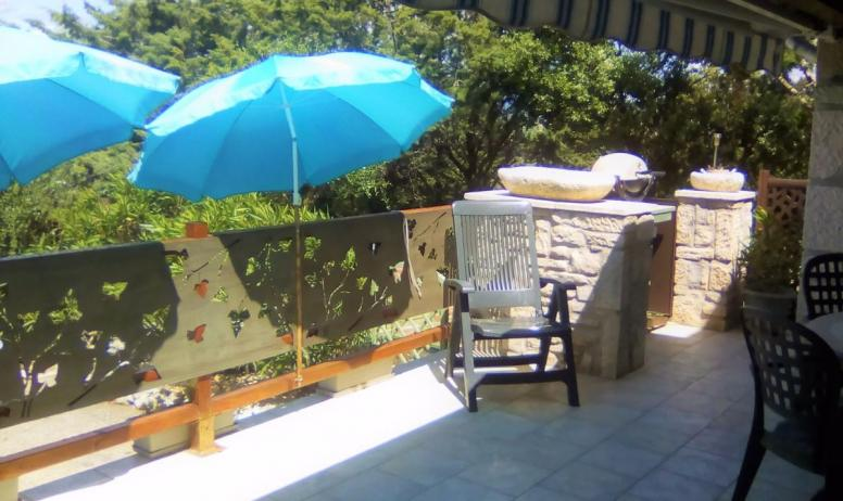 Clévacances - Coin repas de la terrasse avec barbecue