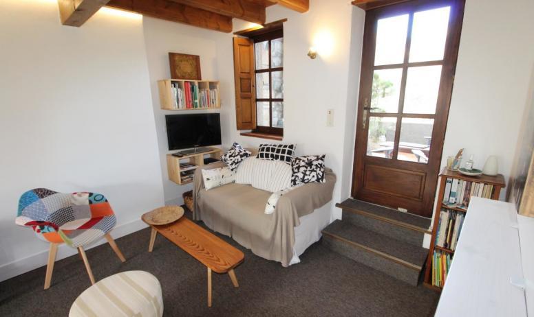 Gîtes de France - Salon avec canapé et TV, porte terrasse vue sur les Sentinelles