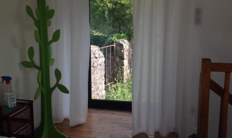 Gîtes de France - La chambre à coucher dans la mezzanine et sa baie donnant sur un espace de verdure